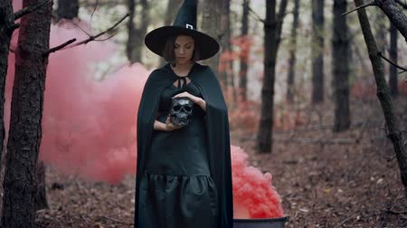 Black witch holding skull in hands, stroking it on autumn smoke forest background. Horror, halloween, cosplay holiday, magic concept Wideo