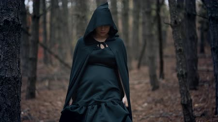 Black witch in hood walks in autumn scary forest.Womanl in long dress. Halloween, horror, concept, cosplay dressing up Wideo