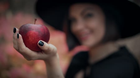 сказка : Woman as witch with an evil grin in black offers red apple as symbol of temptation, poison. Fairy tale concept, halloween, cosplay.