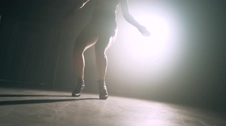 Dancers legs in dark in smoky room of nightclub. Girl dances beautifully and seductively to beat of music. Slow motion.