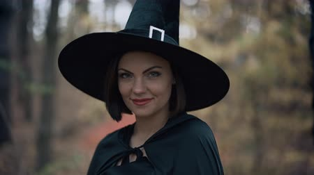 Beautiful witch in cap, long dress, mantle on autumn forest background. Halloween concept, cosplay dressing up. Slow motion