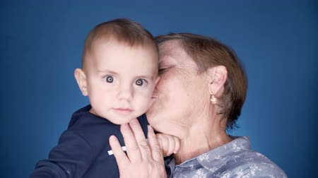 Grandmother with baby boy on blue wall background having fun, smiling, playing. Grandson is happy to communicate with elderly great-grandmother Wideo