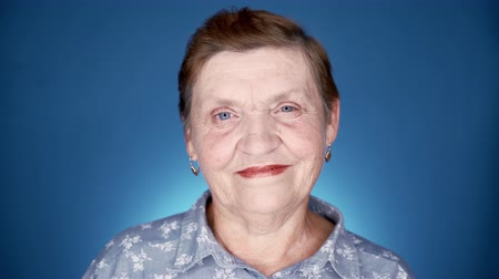 Portrait of smiling aged woman in studio on blue background. Caucasian kind grandmother looking at camera. Wideo