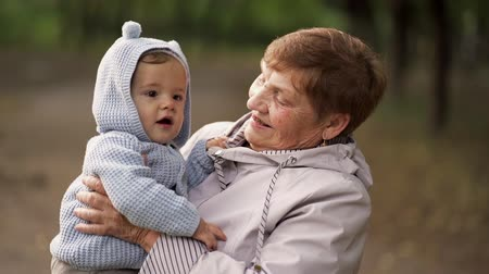 unokája : Grandmother with baby boy in autumn park having fun, smiling, playing. Grandson is happy to communicate with elderly great-grandmother