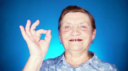 договориться : Beautiful portrait of smiling aged woman on blue background. Caucasian grandmother looking at camera and showing ok sign - gesture of approval.