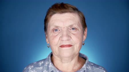 Caucasian kind grandmother looking at camera. Portrait of smiling aged woman in studio on blue background. Wideo