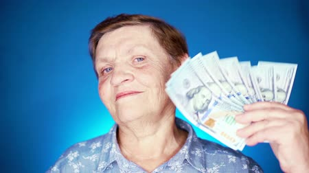 calcular : Grandmother smiling, she happy to get benefits with paper currency. Elderly woman pensioner on blue background with dollars.