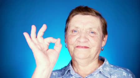 achievements : Beautiful portrait of smiling aged woman on blue background. Caucasian grandmother looking at camera and showing ok sign - gesture of approval.