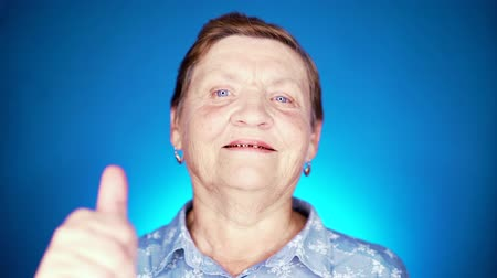 gesticulation : Beautiful portrait of smiling aged woman on blue background. Caucasian grandmother looking at camera and showing thumb-up sign - gesture of approval.