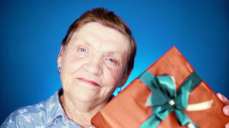 entusiasmo : Grandmother smiling, she happy to get gift box with bow on her birthday or Christmas. Elderly woman pensioner on blue background. Stock Footage