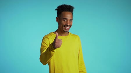 forefinger : Winner.Success.Young man in yellow wear on blue studio background smiles to camera and gives thumbs up. Happy guy showing gesture of approval.