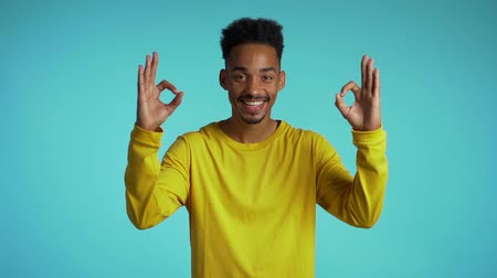 forefinger : Young man making OK sign over blue background. Winner. Success. Positive young african guy smiles to camera. Stock Footage