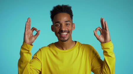 forefinger : Positive young african guy smiles to camera. Young man making OK sign over blue background. Winner. Success. Stock Footage