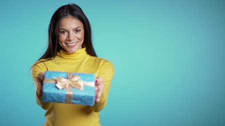 bengália : Pretty brunette woman gives gift and hands it to the camera. She is happy, smiling. Girl on blue background. Positive holiday footage Stock mozgókép