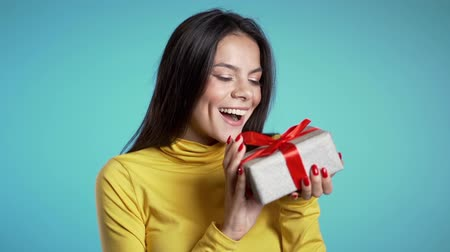 bengália : Excited woman received gift box with bow. She is happy and flattered by attention. Girl on blue background. Studio footage. Stock mozgókép