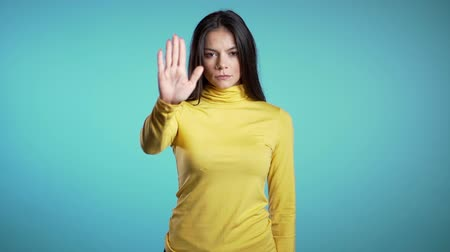 cuidado : Business woman disapproving with NO hand sign gesture. Denying, rejecting, disagree, portrait of beautiful mature girl or student on blue background