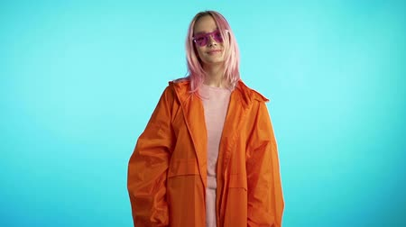 rendkívüli : Cheerful odd girl in blue studio. Smiling woman with nose piercing, sunglasses. Vibrant colorful footage. Slow motion.