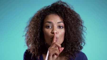 segredo : African american woman holding a finger on her lips over blue background. Gesture of shhh, secret, silence. Close up.