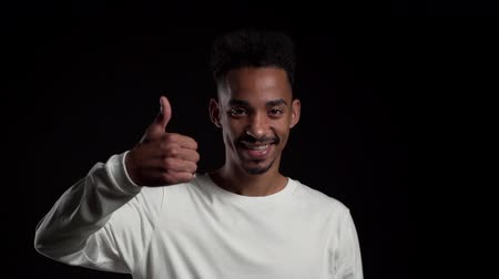 договориться : Handsome man in white wear on black studio background smiles to camera and gives thumbs up. Happy african american guy showing gesture of approval. Winner.Success.