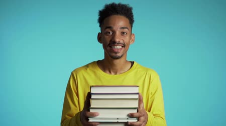 dosya : African student on blue background in the studio holds stack of university books from library.