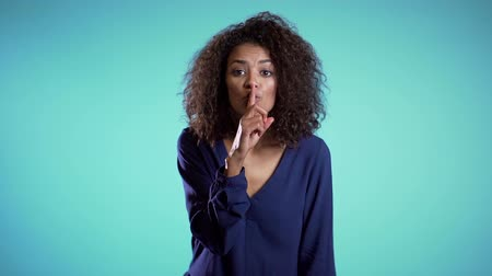 forefinger : African american woman holding a finger on her lips over blue background. Gesture of shhh, secret, silence. Stock Footage