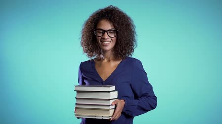 ansiklopedi : African student with glasses on blue background in the studio holds stack of university books from library. Girl smiles, she is happy to graduate. Stok Video