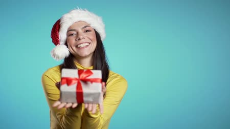bengália : Beautiful cheerful hispanic woman in Santa hat holds out gift box to you on blue background. Christmas, New year holiday concept.