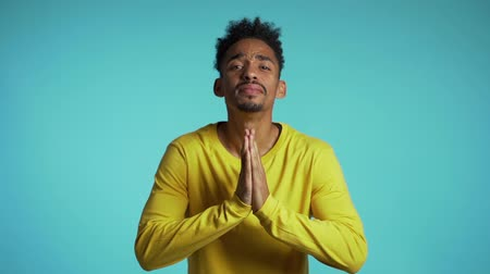 pleading : Handsome african american man in yellow t-shirt praying over blue background. Stock Footage