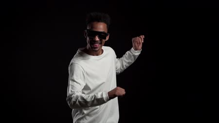 emelt : Young african american man in glowing glasses smiling and dancing in good mood on blue background.