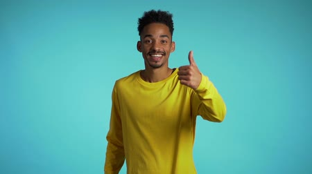 договориться : Handsome black man in yellow wear on blue studio background smiles to camera and gives thumbs up.