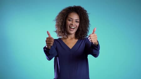 договориться : Businesswoman showing gesture of approval. Winner. Success. Positive young african girl on light blue background smiles for camera and gives thumbs up.