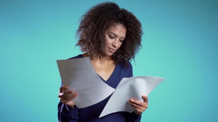 épuisement professionnel : Pretty african american female boss checks documents, utility bills. Serious businesswoman standing on blue background. She is satisfied with work of staff.