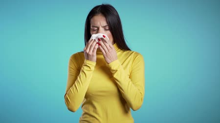 латина : Young hispanic girl sneezes into tissue. Isolated woman is sick, has a cold or has allergic reaction. Health, medicine, illness, treatment concept