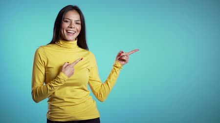 exibindo : Happy smiling woman in yellow wear presenting and showing something isolated on white background. Portrait of girl, she pointing with arms on her left with copy space. Stock Footage