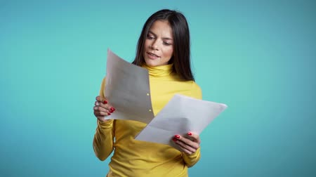 hasznosság : Serious businesswoman standing on blue background. She is satisfied with work of staff. Pretty hispanic female boss checks documents, utility bills.