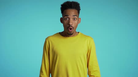 étonnement : Amazed mixed race man shocked, saying WOW. Handsome african american guy with afro hair surprised to camera over blue background. Vidéos Libres De Droits