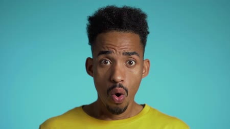 ámulat : Amazed mixed race man shocked, saying WOW. Handsome african american guy with afro hair surprised to camera over blue background. Stock mozgókép