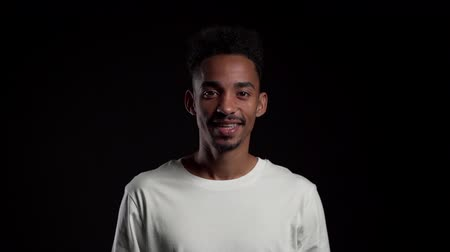 aprovado : Young african american man in white on black studio background showing yes sign by head. Positive footage, emotions, body language concept.