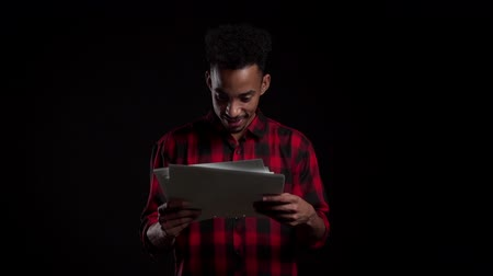 jóváhagyott : African american modern businessman standing on black background. He is satisfied with work of staff. Handsome male boss checks documents, utility bills.