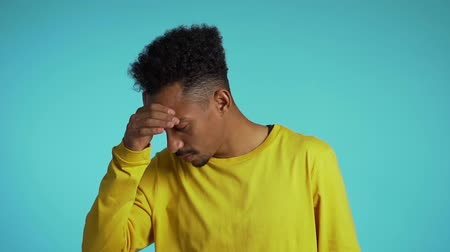 irritáció : Young student man with afro hair having headache, studio portrait. Guy putting hands on head, isolated on blue background.