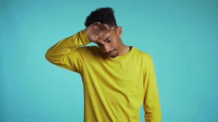 vyčerpání : Frustrated african american man in yellow wear over blue wall background. Guy is tired of work or studying, he disappointed, helpless