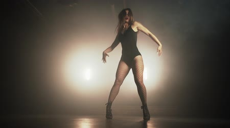 striptease : Young woman in black bodysuit with net pantyhose moves plasticity to music in dark room.Concept of sexual dancing,choreography,art. Stock Footage