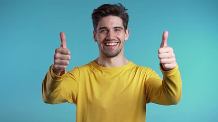 čtvrtý : Handsome young man in yellow wear smiles to camera. Hipster guy showing thumb up sign over blue background.