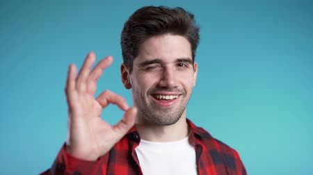 čtvrtý : Positive young man smiles to camera. Hipster guy showing OK sign over blue background. Dostupné videozáznamy
