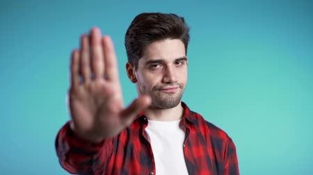 diffidenza : No, never, handsome brunette man disliking and rejecting gesture by stop sign. Slow motion. Portrait of young successful confident guy isolated on blue Filmati Stock
