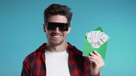 выигрыш : Happy european man in glowing with dollar signs glasses showing money in envelope - U.S. currency dollars banknotes on blue wall. Symbol of success, gain, victory. Slow motion