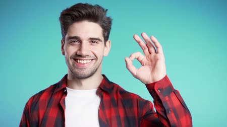 čtvrtý : Handsome young man in red plaid shirt smiles to camera. Hipster guy showing OK sign over blue background. Winner. Success. Body language.