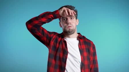 pesadelo : Frustrated european man in red wear over blue wall background. Guy is tired, bored of work or studying, he disappointed, helpless