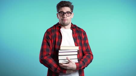 descuidado : European student on blue background is dissatisfied with amount of homework and books. Man confused, he is annoyed, discouraged frustrated by studies. Stock Footage