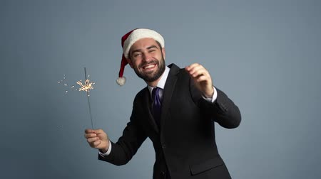fire suit : Portrait of handsome businessman in suit and Santa hat with bengal sparkler fire dancing isolated on studio background. Young happy man with beard celebrate Christmas or New year party.